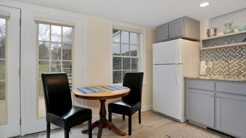 Small dining table and two black leather chairs next to a glass door and window, full-size fridge, and granite counter top with sink, cabinets, and tile backsplash.