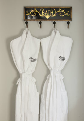Two Brewster By The Sea Inn bathrobes hanging on a hook