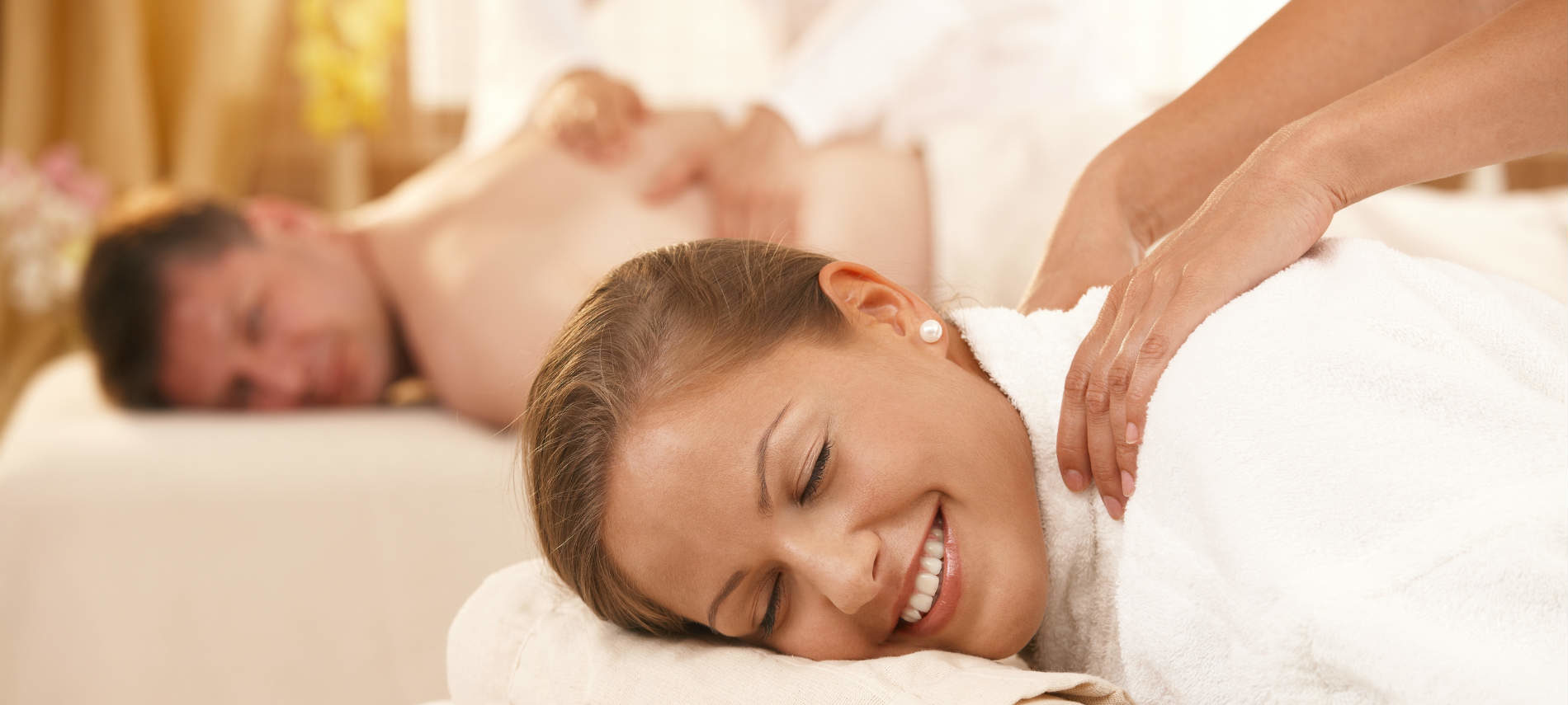 Woman getting a massage while laying down and wearing a robe with a man getting a massage in the background
