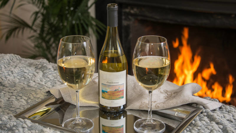 Fireplace in Emerson room in the background with two glasses of Chardonnay and the bottle on a silver platter