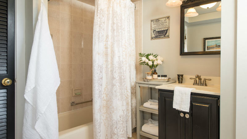 The bathroom of Garden Room showing a full tub with shower curtain, sink with cabinets and mirror above, and a towel hanging off a hook