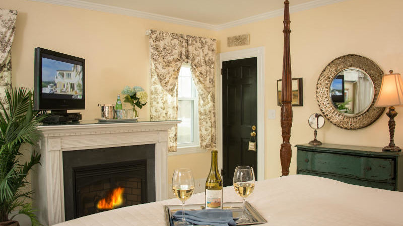 Two glasses of wine on a platter on a bed in the Garden Room, with a TV above a lit fireplace