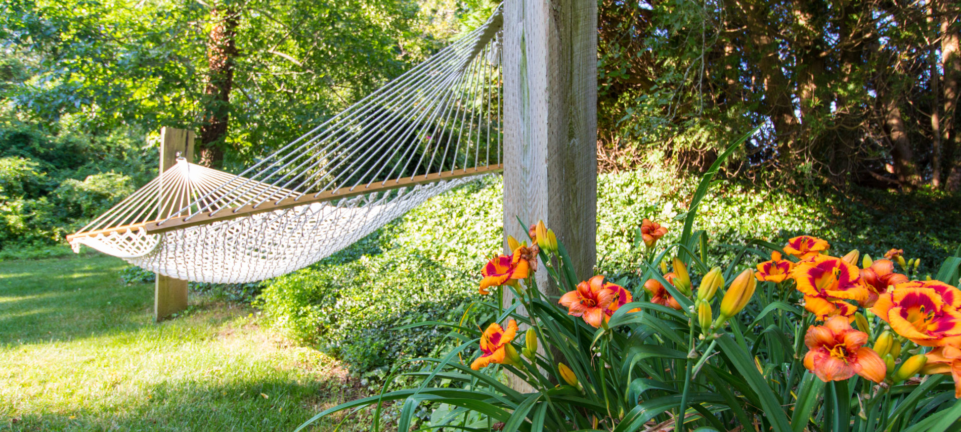 Hammock over green grass next to a garden at Brewster By The Sea Inn