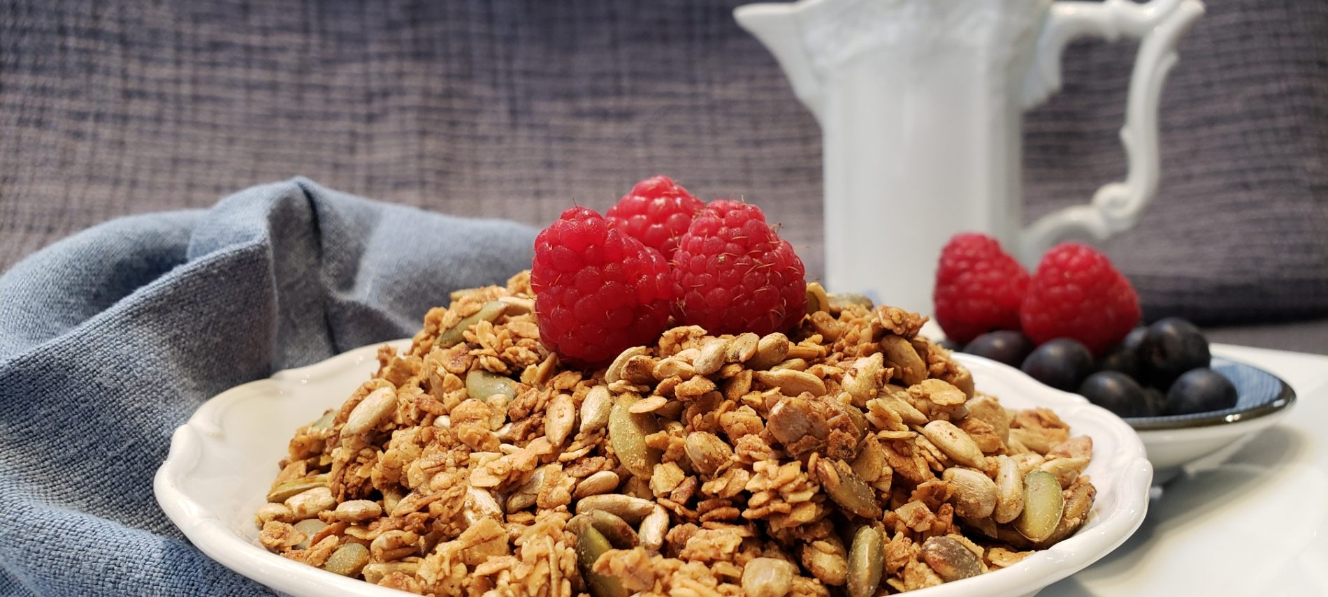 A bowl of granola with berries in a bowl on a napkin