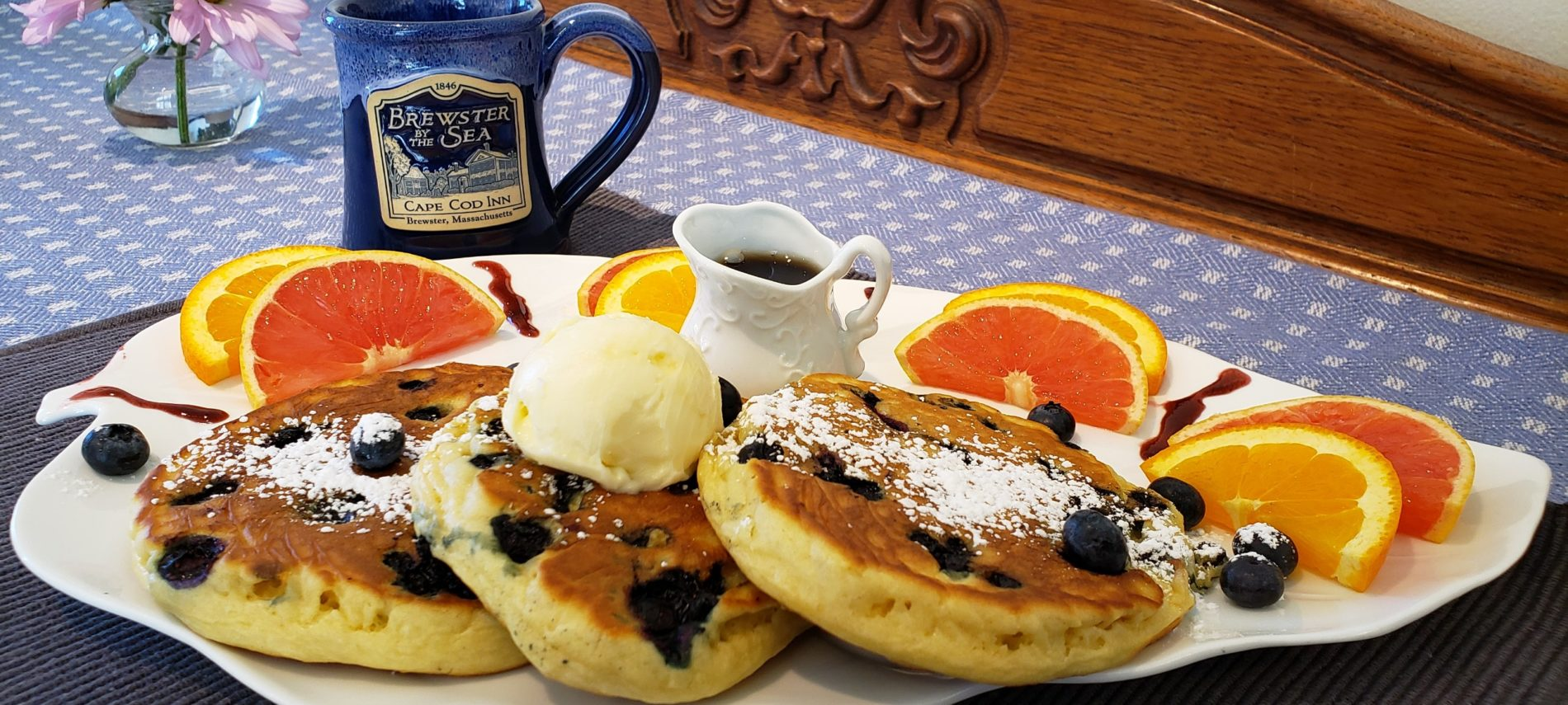 Blueberry Crumb Pancakes on a plate with orange slices and maple syrup