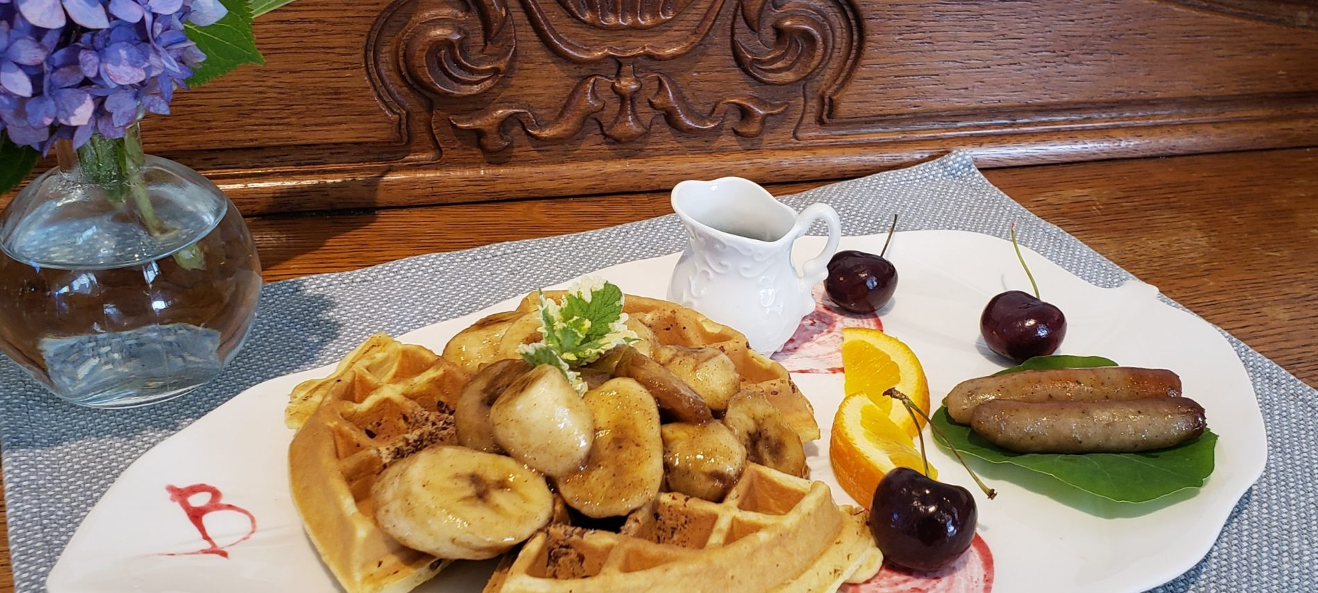 Waffles with Bananas Foster Sauce on top and a size of fruit and sausage on a plate on top of a wooden table