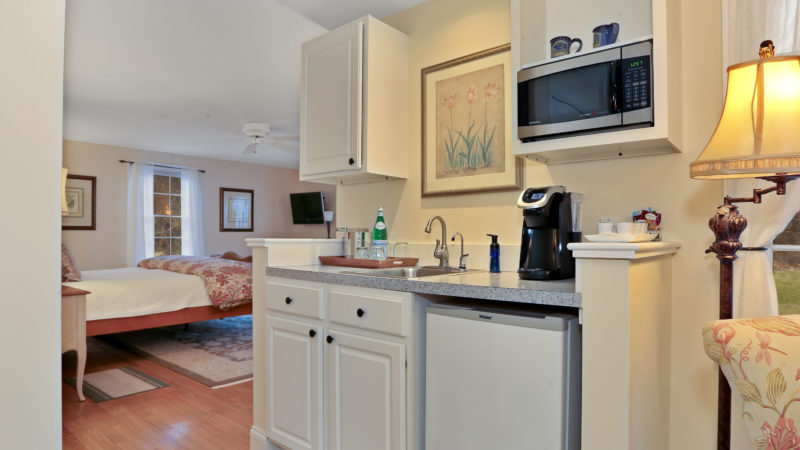Refugio Suite kitchenette with a sink, mini fridge, cabinets, microwave, and the bed and TV in the background.