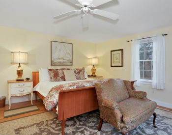 Refugio Suite bedroom with a bed, lounge chair, nightstands with lamps, ceiling fan, and windows with sheer curtains.