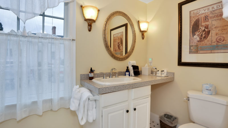 The Refugio Suite bathroom showing a gray countertop with sink, toilet, mirror, and a window with white sheer curtains.