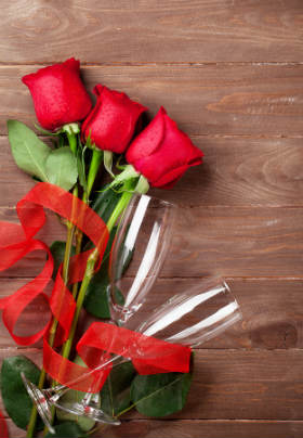 Red roses and empty champagne flutes laying on a wooden table