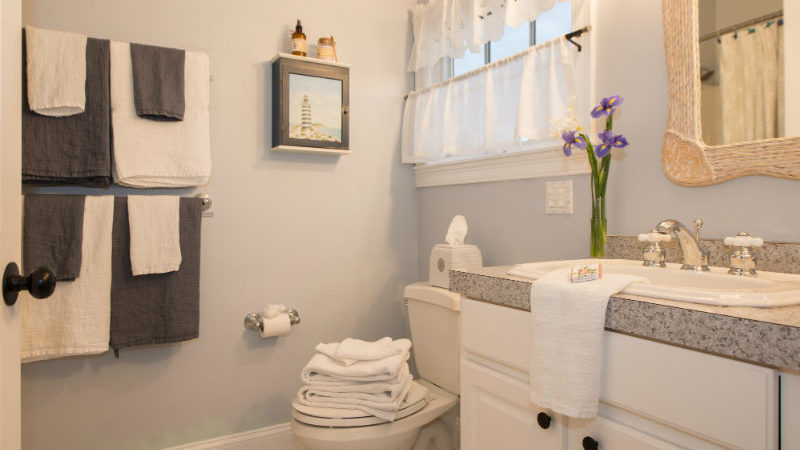 The bathroom of Sea Meadow Room showing a gray countertop with sink and flowers, a mirror above the sink, toilet, towels hanging from two racks, and a small window with white curtains..
