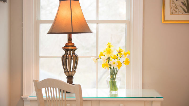 Daffodils on a white desk in Sea Meadow Room in front of a bright window