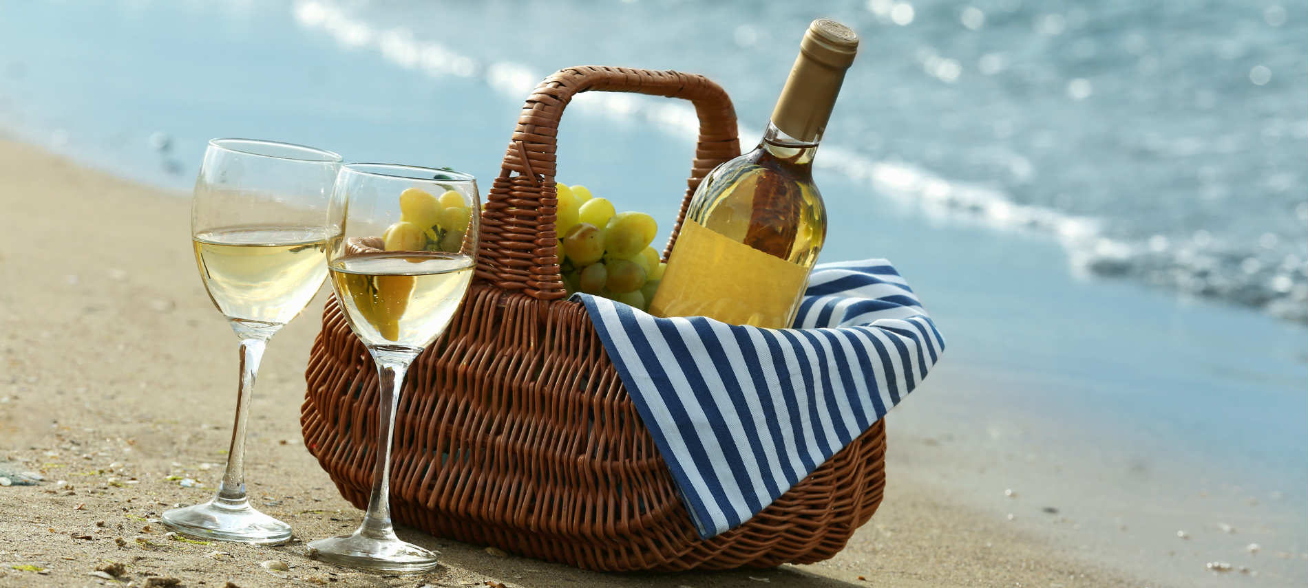 Basket filled with wine and grapes on a beach next to two glasses of white wine