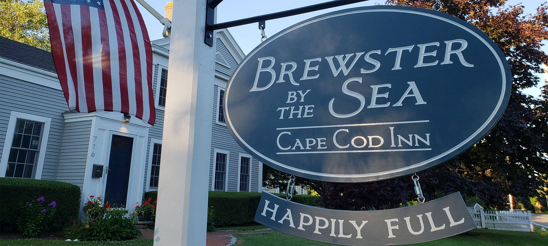 A closeup of the blue sign at Brewster By The Sea Inn