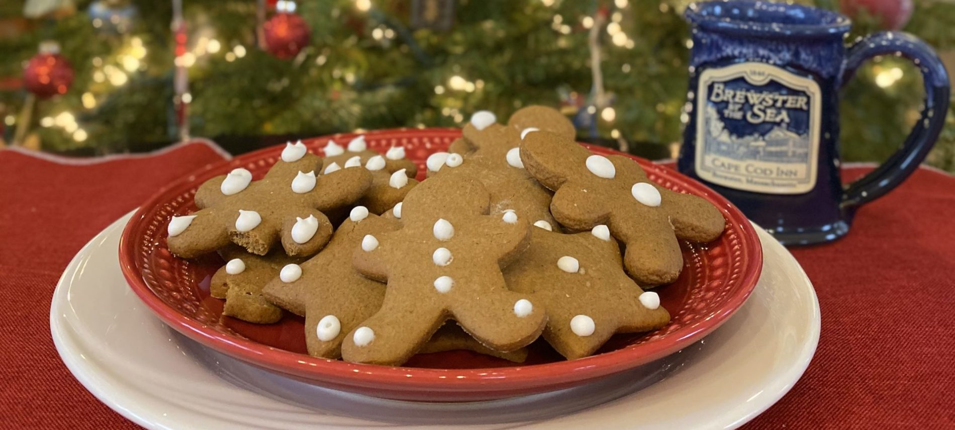 Gingerbread cookies on a plate in front of a Christmas tree