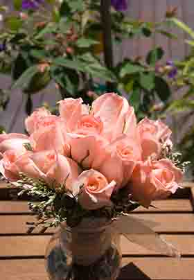 Pink roses outside in a vase on a table