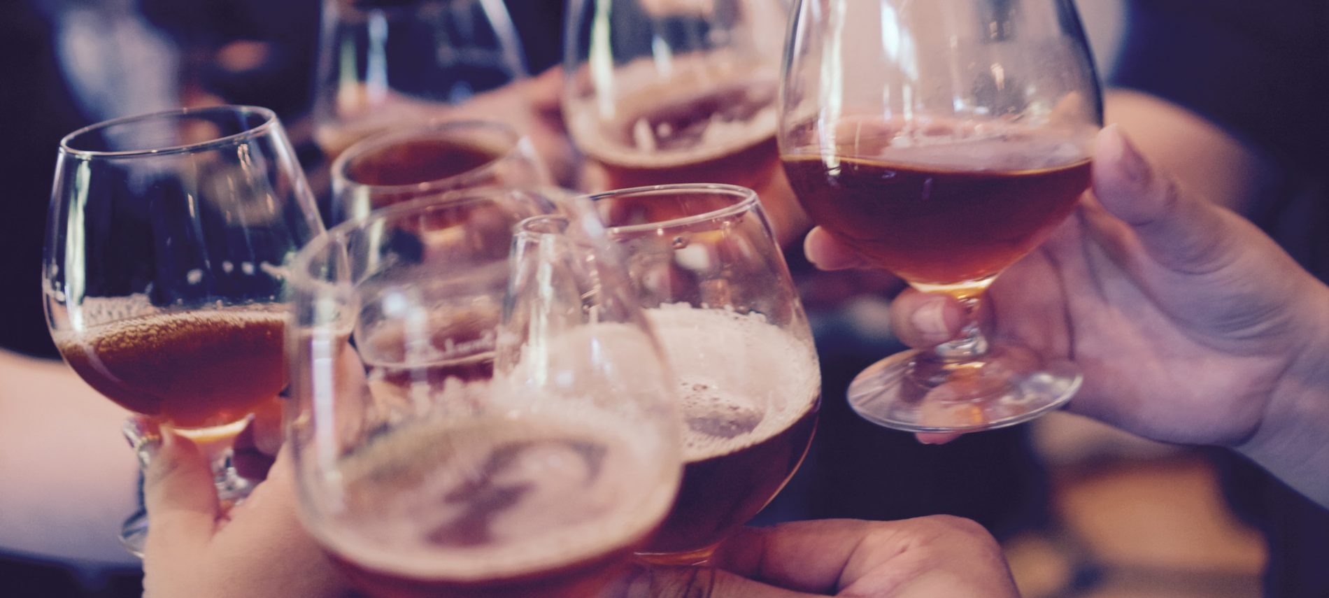 Hands cheersing small glasses of beer