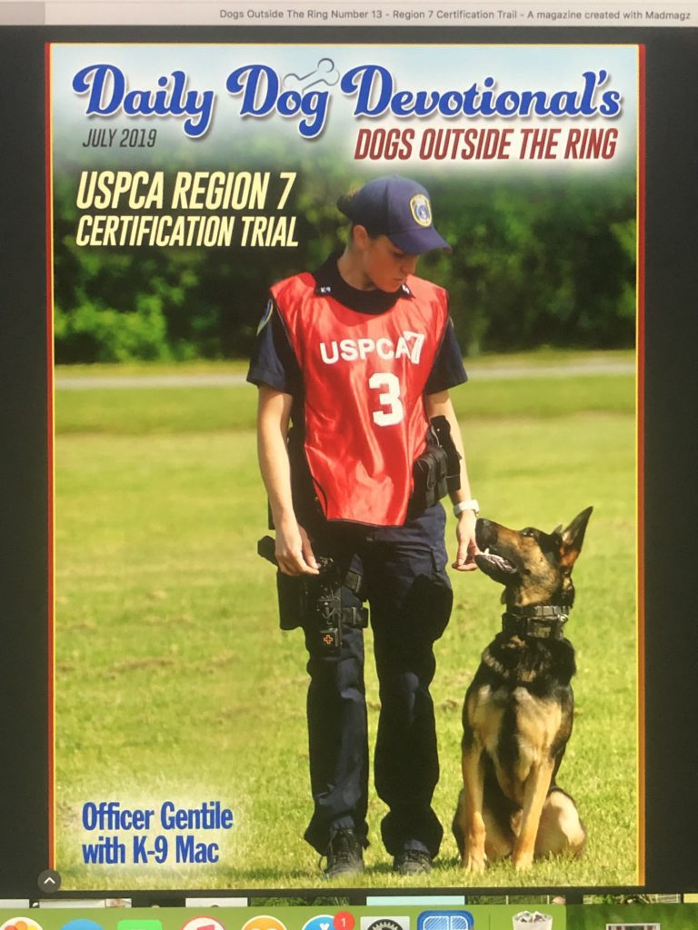 Female police officer wearing a red jersey and a German Shepard police dog in the front cover of a magazine