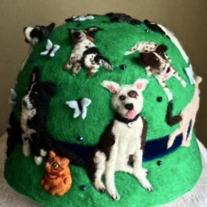 Green derby hat with figures of different dog breeds stitched on it