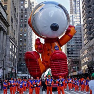 Big float of Snoopy wearing a red and orange astronaut suit being pulled by hundreds of people in orange and blue uniforms