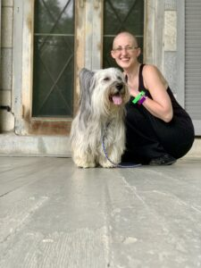 Bald woman dressed in black sitting down to pet a Skye Terrier