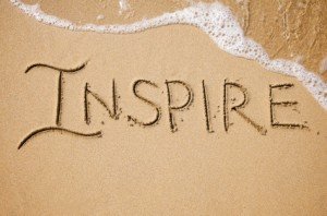 The word Inspire written in the sand.