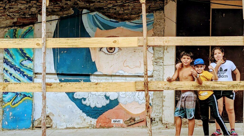 Kids playing near fading Street Art