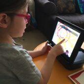 child with red glasses using an ipad to draw circles