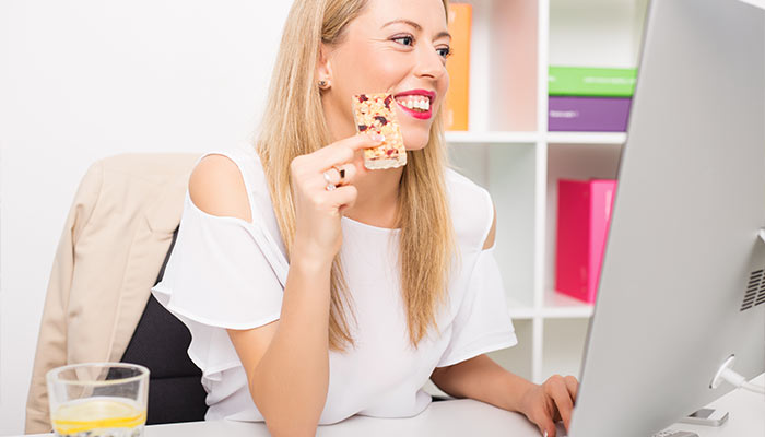 woman sitting at desk and eating a protein bar