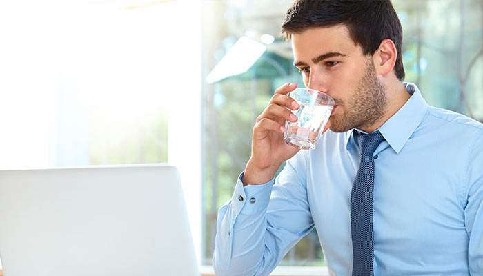 businessman drinking water while on laptop