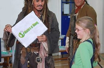 Johnny Depp Wearing Pirates of The Caribbean Costume Holding Masters of Money LLC Logo Sign