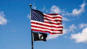 American and POW flags flying on a flagpole against a blue sky and white clouds.