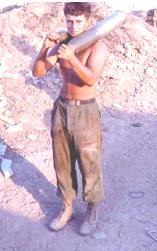 Specialist 4 Tom Garvey carrying 105mm shells in Vietnam.