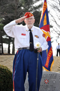 Photo of Marine Corps Veteran Jerry Ingram saluting at a remembrance ceremony.