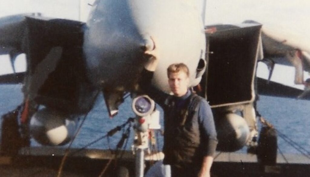 Petty Officer Jim McCune standing by an F-14 aboard USS KITTY HAWK