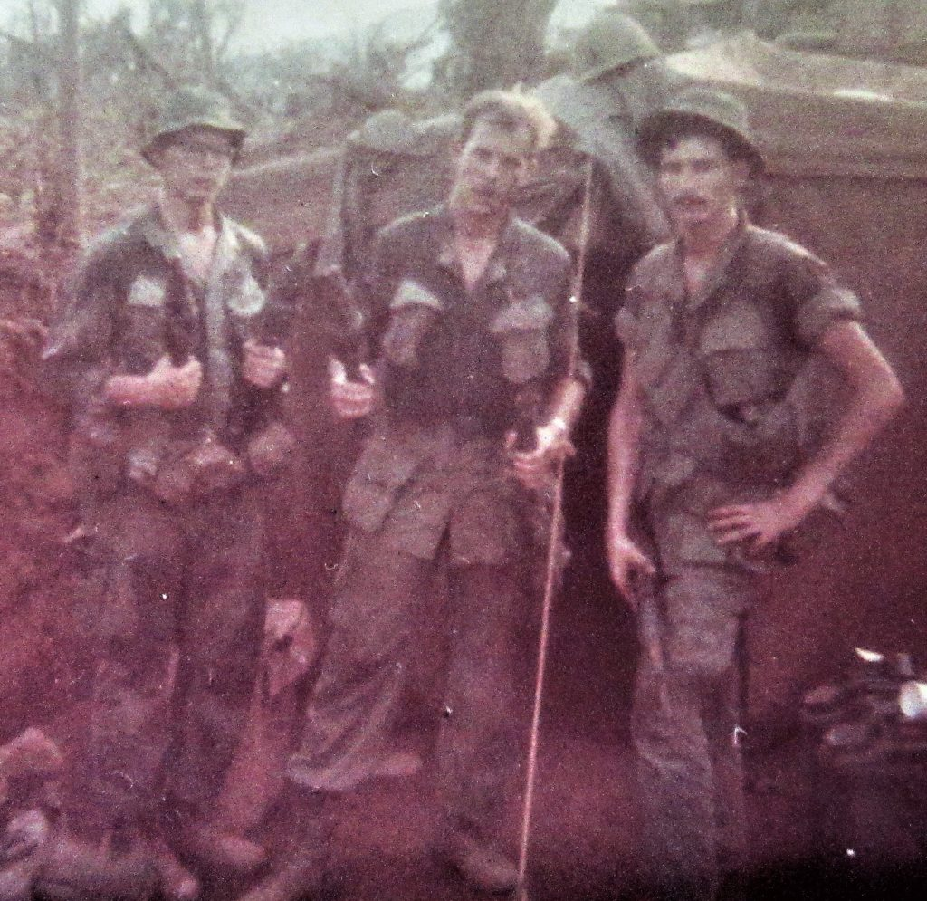 Dave Anson with two other soldiers holding captured weapons.