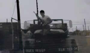 Paul Schuler with rifle on jeep