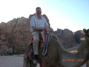 Photo of Dave Grogan riding a camel in Petra, Jordan