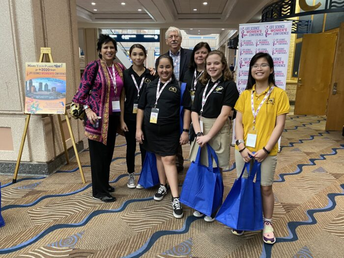 Cherie Mathews, Steve Fiske, and four young high school girls interested in STEM standing together in front of the Life Science Women's Conference 2020 sign.