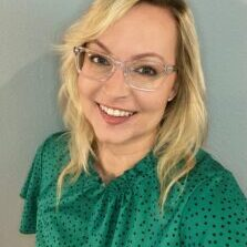 Catherine Marten, with shoulder-length blonde hair, a bright green top dotted with black, and clear square glasses.