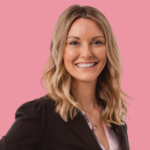 An image of Mary Kucek smiling against a soft pink background.