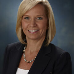 A headshot of Melissa Seymour, smiling, with shoulder-length blonde hair and a black blazer.