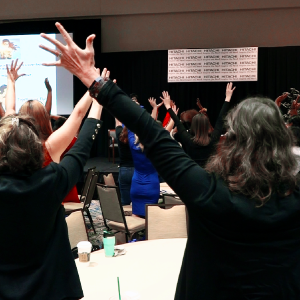 Attendees standing in the main stage area, raising their arms up in solidarity.