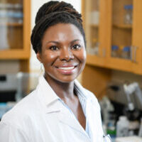 A headshot featuring Dr. Renee Cottle, hair up in a bun, smiling brightly as she wears her lab coat.