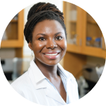 A headshot of Dr. Renee Cottle, proudly wearing her lab coat. Her hair is wrapped up in a high bun.