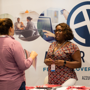 A photo of an exhibitor talking with an attendee.