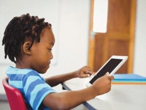 Young boy holding and looking at an ipad