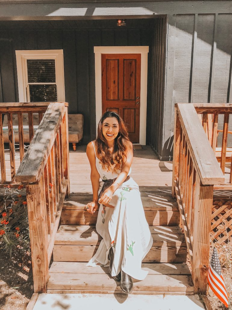 Alexis Alcala sitting on the porch of her air bnb in Los Alamos California