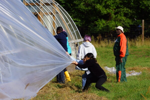 Students construct a plastic pull hoop house during WEI's Will Allen Farmer Training Weekend