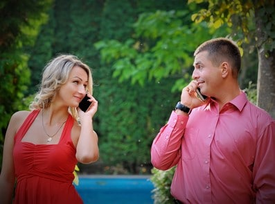 Young couple successful businessmen agree on the best deal. He was talking on the phone, it searches the internet for new business partners.